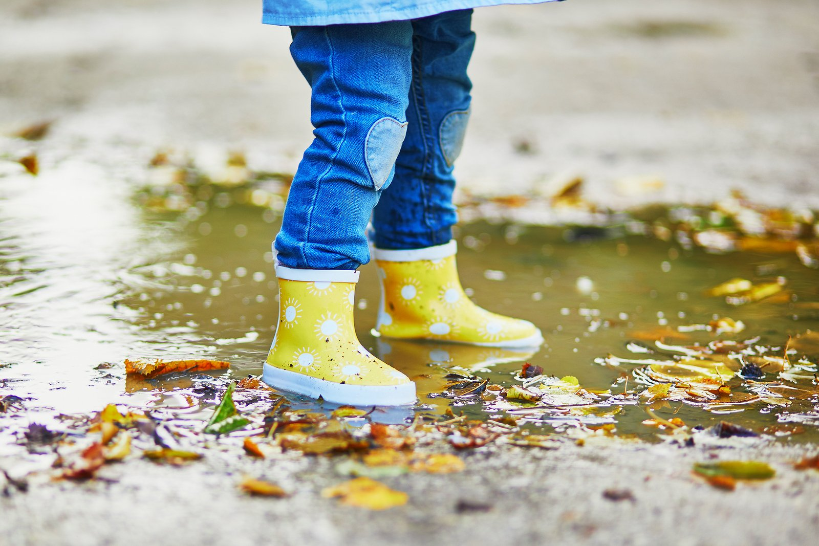 kid with rain boot standing in puddle
